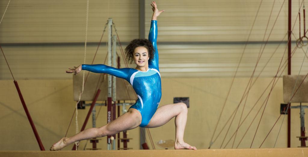 Turnerin in eleganter Pose au dem Balken mit einem schönen blauem Turnanzug dynamischem Design vom ERVY Made in Germany